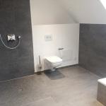 Toilette neben dem gefliesten Duschbereich