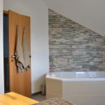 Badewanne mit Natursteinwand