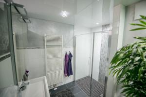 Badezimmer mit Hochglanz-Fliesen und Mosaik